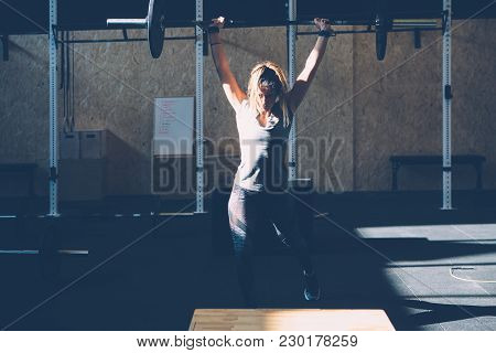 Young Woman Athlete Doing Jerks With Barbell At Box Gym On A Fitness Routine