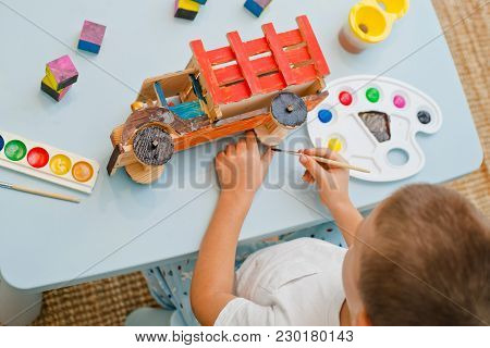 Child At The Table Paints A Wooden Model Of A Truck