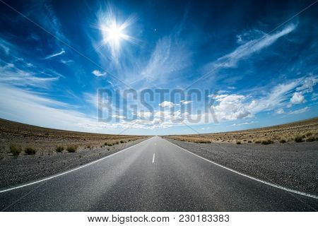Asphalt road in the desert and sky with clouds. Road 3 (Ruta 3) through the Argentinean pampa.