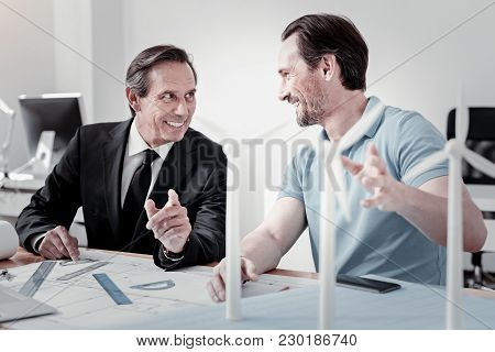 Pleasant Conversation. Enigmatical Elderly Man Keeping Smile On His Face And Actively Gesticulating