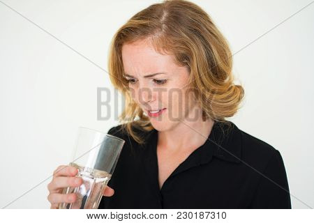 Confused Young Woman Examining Water In Glass Before Drinking. Concentrated Girl Displeased With Qua