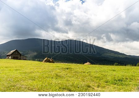 Mountain Glade With A House From A Log House And Sheaves Of Hay. Mountain Landscape.