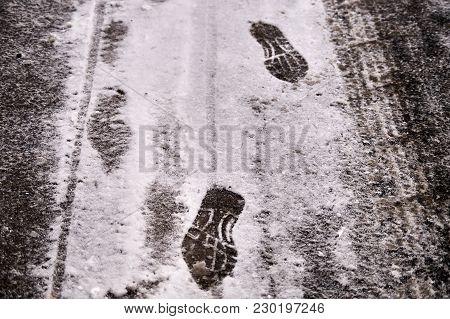 Shoe Footprints In Snow On Winter Asphalt Road.