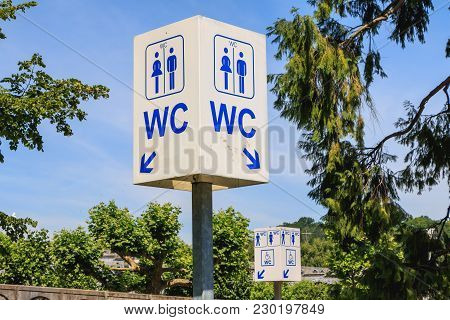 Street Toilet Sign, Tourists Help Service On Blue Sky In France
