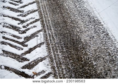 Tractor And Car Tracks In Snow On Winter Asphalt Road.