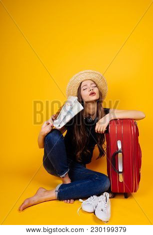 Astounded Woman Tourist Sits Next To A Red Suitcase, Vacation