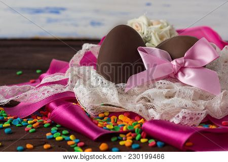Chocolate Eggs, White Lace Tape, Pink Tape, Color Sweets, On The White Wooden Background. Easter Con