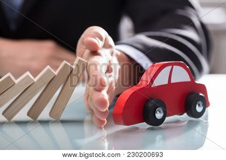 Businessperson's Hand Stopping Wooden Blocks From Falling On Car