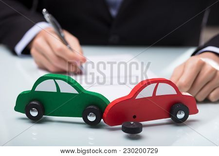 Close-up Of Red And Green Car In Front Of Businessman Writing On Paper