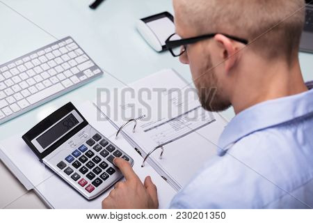 Businessman Using Calculator For Calculating Invoice At Desk