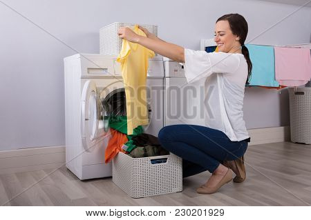 Happy Young Woman Looking At Cleaned Yellow Tshirt After Washing In Washing Machine
