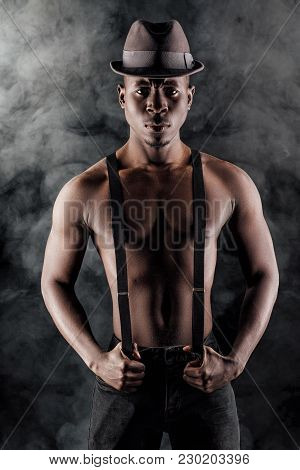 Afro-american Man Topless In Hat And Suspenders On Black Background.