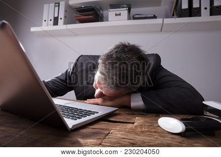 Businessman Sleeping In Office With Laptop On Wooden Desk