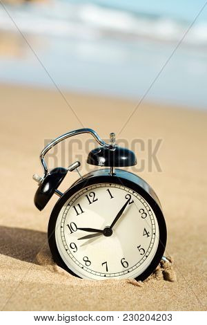 closeup of an alarm on the sand of the beach, adjusting the time forward or backward one hour, at the beginning or at the end of the daylight savings time