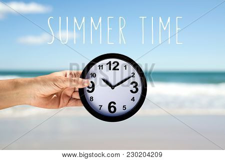 closeup of a young caucasian man with a clock in his hand on the beach, next to the seashore, and the text summer time