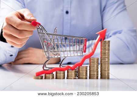 Increasing Graph Of Coins In Front Of Human Hand Holding Small Shopping Cart
