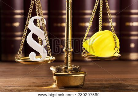 Close-up Of White Paragraph Symbol And Yellow Hard Hat On Justice Scale