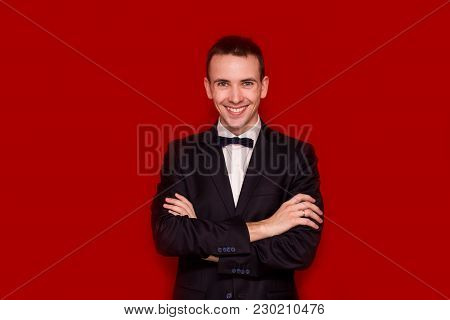 Portrait Of Smiling Handsome Stylish Man In Elegant Black Suit On Red Background. Business Style. Fa