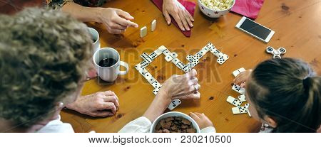 Top View Of Grandmother, Daughter And Granddaughter Playing Domino In The Living Room