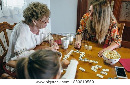 Grandmother, Daughter And Granddaughter Playing Domino In The Living Room