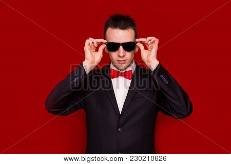Portrait Of Serious Handsome Stylish Man In Elegant Black Suit On Red Background. Business Style. Fa