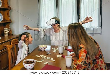 Senior Woman Using Virtual Reality Glasses With Her Daughter And Granddaughter