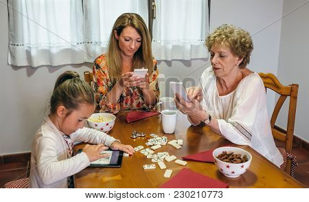 Grandmother, Daughter And Granddaughter Using Tablet And Smartphone