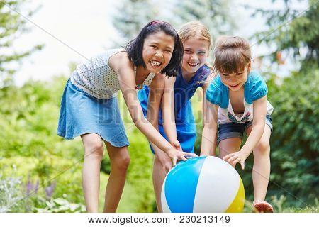 Three girls as friends roll ball in teamwork and have fun in summer