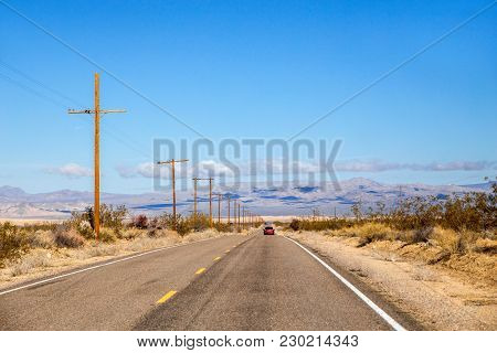 Three Cars Travelling Along A Narrow Highway With Mountains In The Background In A Spring Desert Lan