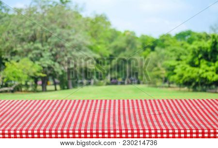 Empty Table With Red Tablecloth Over Blur Garden And Bokeh Background, For Food And Product Display
