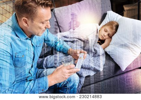 Necessary Pills. Attentive Caring Father Sitting On The Sofa With A Pillbox In His Hand And Looking