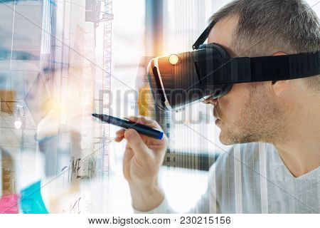 Concentrated Man. Clever Attentive Young Man Wearing Amazing Virtual Reality Glasses And Feeling Ser