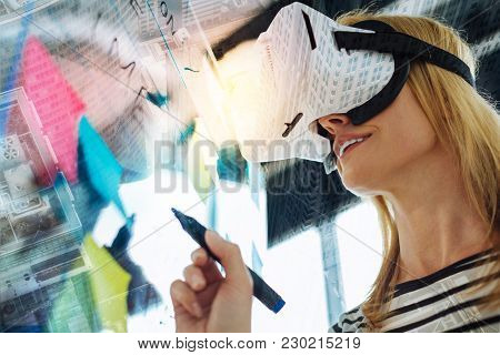 Amazing Device. Clever Emotional Progressive Woman Discovering Virtual Reality And Smiling While Sta