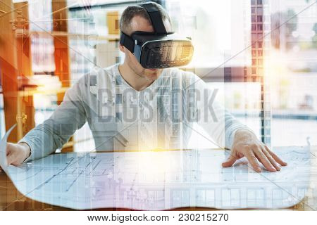 New Drawing. Clever Experienced Architect Sitting At The Table And Wearing Virtual Reality Glasses W
