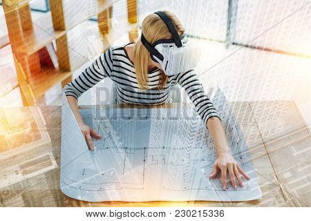Convenient Scheme. Calm Clever Attentive Engineer Wearing Virtual Reality Glasses While Sitting At T