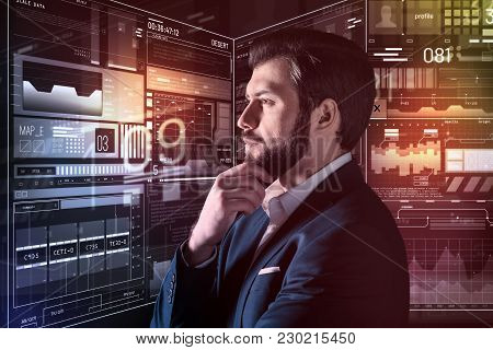 Thoughtful Person. Calm Concentrated Young Programmer Attentively Looking At The Screen Of His Futur