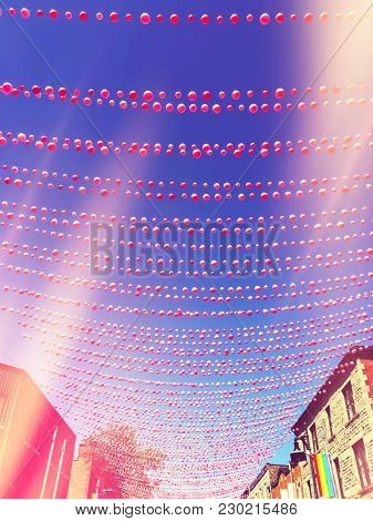 Retro Style Image Of A Street In Gay Neighborhood Decorated With Pink Balls, With Light Leaks Effect