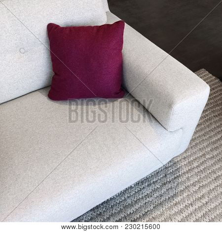 White Sofa With Cherry Red Cushion, On A Gray Knitted Rug.