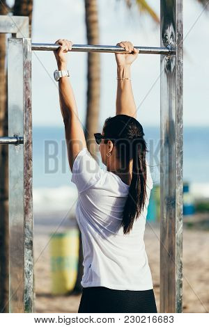 Fitness Woman Exercising On Chin-up Bar. Lady Doing Chin-ups Outside On Beach In Summer
