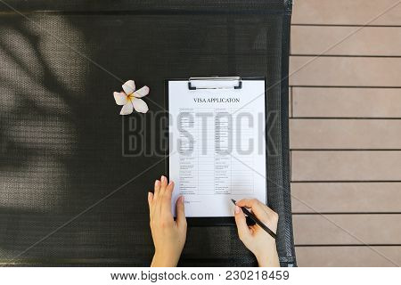 Beautiful Sunshine Portrait Of Woman Hands Hold Pen And New Visa Application Form For Travel. Concep