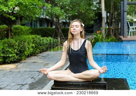 Fitness Healthy Woman Sit In Lotus Position Doing Yoga By Swimming Pool On Sunny Day. Concept Of Phy