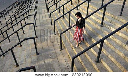 Beautiful Brunette Woman In Red Striped Pleated Skirt Is Running Downstairs. City Life Urban People