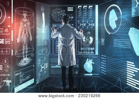 Careful Worker. Attentive Young Medical Worker Carefully Touching The Futuristic Transparent Screen