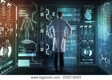 Thoughtful Doctor. Qualified Experienced Smart Doctor Standing In Front Of A Futuristic Device And T