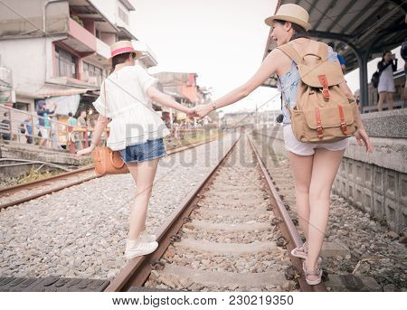 Attractive Trendy Young Women Having Fun Balancing On A Railway Line Holding Hands In An Attempt To