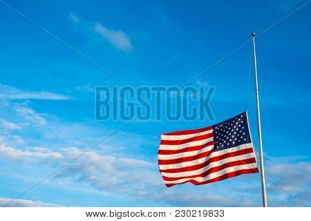 American Flag At Half Mast Under Perfect Lighting And Perfect Blue Sky. A Patriotic National Symbol