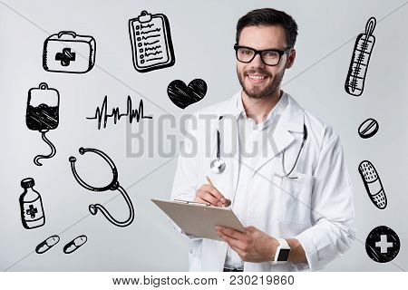 Writing Prescription. Clever Experienced Friendly Doctor Standing With A Clipboard In His Hand And S