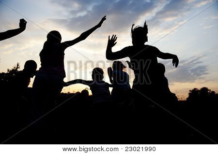 Group of happy children dancing on meadow, sunset, summertime
