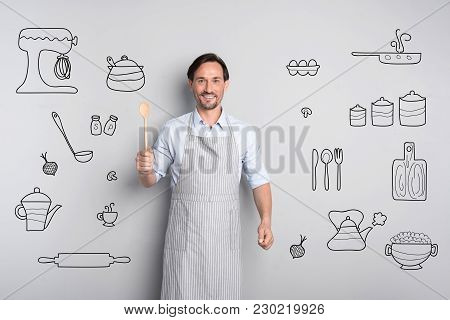 Positive Cook. Enthusiastic Experienced Professional Cook Feeling Glad And Smiling While Standing In