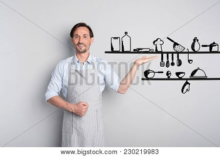 Necessary Dishes. Qualified Experienced Cook Looking Confident While Standing Next To The Shelf And